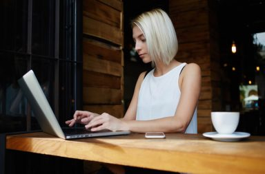 Young attractive lady keyboarding something on portable net-book while sitting in coffee shop during work break, beautiful smart female student using laptop computer to prepare for the coursework