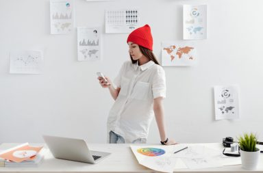 Young female designer working with gadgets and infographics
