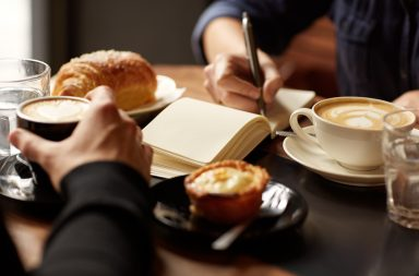 Cropped image of two people's hands at a table with coffees and pastry snacks, one person picking up their espresso while the other is writing in a notebook, possibly taking down an interview